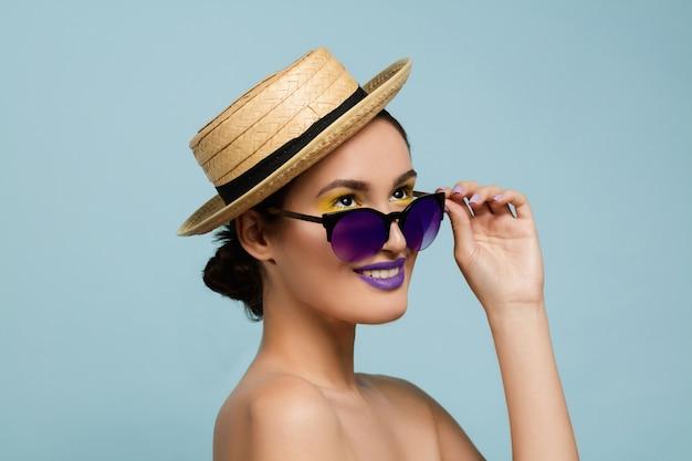 青いスタジオの背景に明るいメイク、帽子、サングラスの美しい女性の肖像画。スタイリッシュでファッショナブルなメイクとヘアスタイル。夏の色。美容、ファッション、広告のコンセプト。レトロ。