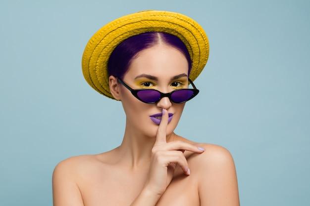 밝은 메이크업, 모자와 선글라스 블루 스튜디오 배경에 아름 다운 여자의 초상화. 세련되고 세련된 메이크업과 헤어 스타일. 여름의 색상. 미용, 패션 및 광고 개념. 비밀.