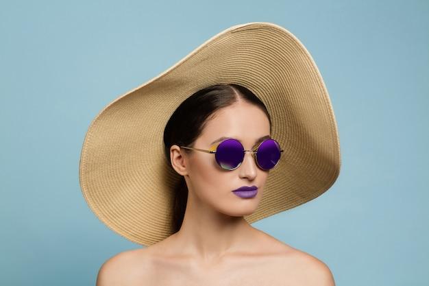 밝은 메이크업, 모자와 선글라스 블루 스튜디오 배경에 아름 다운 여자의 초상화. 세련되고 세련된 메이크업과 헤어 스타일. 여름의 색상. 미용, 패션 및 광고 개념. 진지한.