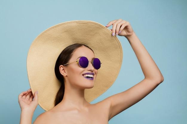 블루 스튜디오에 밝은 메이크업, 모자와 선글라스와 아름 다운 여자의 초상화