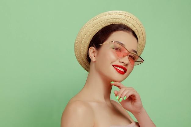 밝은 메이크업, 모자와 선글라스 녹색 스튜디오 배경에 아름 다운 여자의 초상화. 세련되고 세련된 메이크업과 헤어 스타일. 여름의 색상. 미용, 패션 및 광고 개념. 웃고.