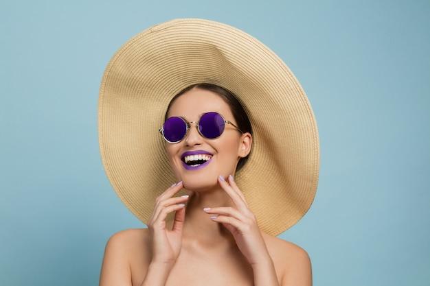 明るいメイク、帽子、サングラスの美しい女性の肖像画。スタイリッシュでファッショナブルなメイクとヘアスタイル。夏の色。笑う。