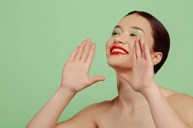 밝은 메이크업, 빨간 안경 및 녹색 스튜디오 배경에 모자와 아름 다운 여자의 초상화. 세련되고 세련된 메이크업, 헤어 스타일. 미용, 패션 및 광고 개념. 판매를 요청하고 웃고 있습니다.