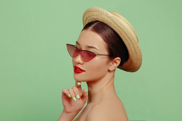 밝은 메이크업, 빨간 안경, 모자와 아름 다운 여자의 초상화. 세련되고 세련된 메이크업과 헤어 스타일. 여름의 색상. 포즈.