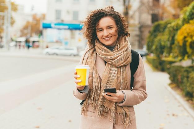커피 한잔 들고 곱슬 머리를 가진 아름 다운 여자의 초상화 빼앗아 카메라를 찾고