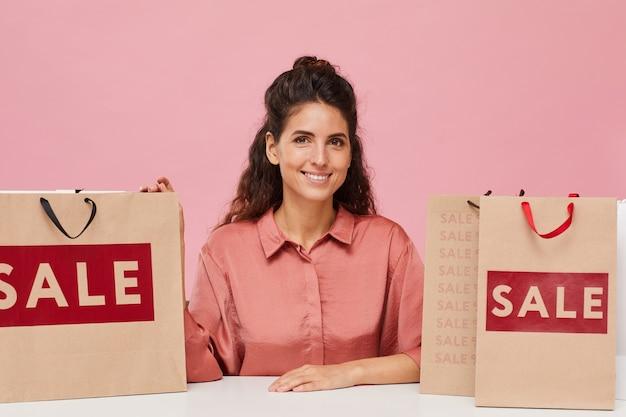 ショッピングバッグとテーブルに座ってカメラに笑みを浮かべて巻き毛の美しい女性の肖像画