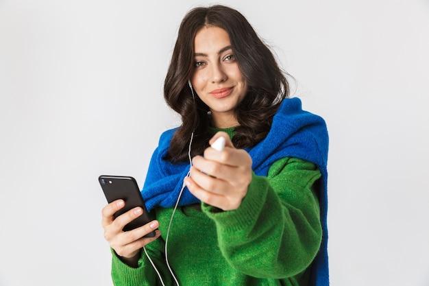 흰색에 격리하는 동안 이어폰을 착용하고 휴대 전화를 들고 검은 머리를 가진 아름 다운 여자의 초상화
