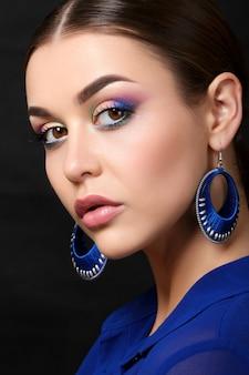 青いイヤリングを身に着けているファッションメイクと美しい女性の肖像画。現代のファッションメイク。カラフルなスモーキーアイ。