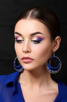 블루 귀걸이를 착용하는 패션 메이크업으로 아름 다운 여자의 초상화. 현대 패션 메이크업. 화려한 스모키 눈.