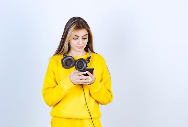 휴대 전화를 사용하여 헤드폰을 끼고 있는 아름다운 여성의 초상화