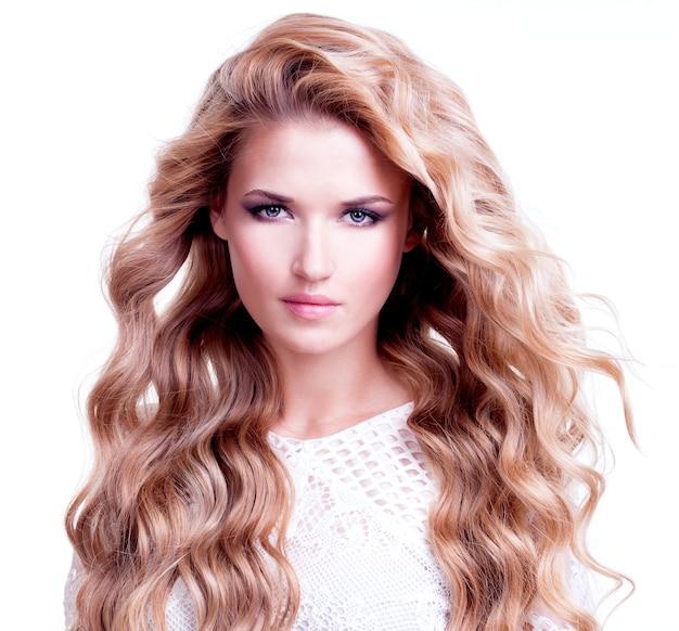 長いブロンドの巻き毛を持つ美しい女性の肖像画。白い壁にポーズをとるファッションモデル。