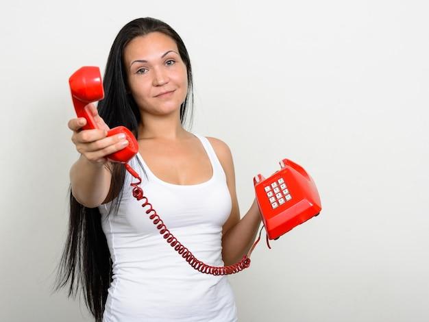 Портрет красивой женщины со старым телефоном у белой стены
