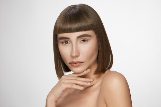 완벽 한 피부를 가진 아름 다운 여자의 초상화, 흰색 배경에 짧은 머리와 화려한 여성