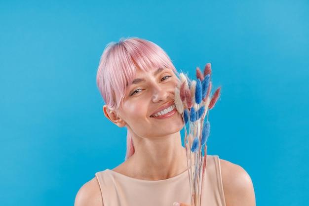 Портрет красивой женщины с розовыми волосами, улыбаясь в камеру, держа в руке сушеную пампасную траву