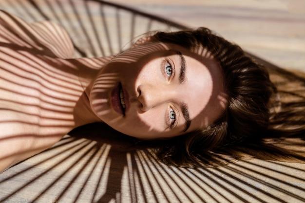 Портрет красивой женщины с тенями пальмового листа на ее лице. концепция принятия солнечных ванн, отдыха.