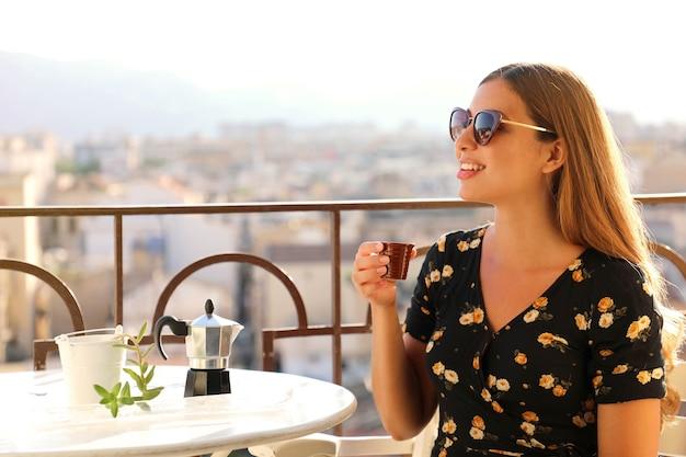 夕暮れ時にイタリアンコーヒーを飲むテラスに座っているサングラスと美しい女性のポートレート