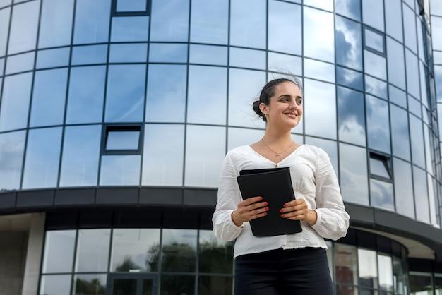 Портрет красивой женщины с планшетом на открытом воздухе возле большого офисного центра