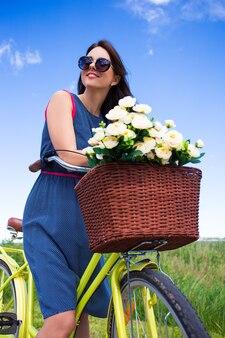 ヴィンテージ自転車と籐のバスケットの花と美しい女性の肖像画