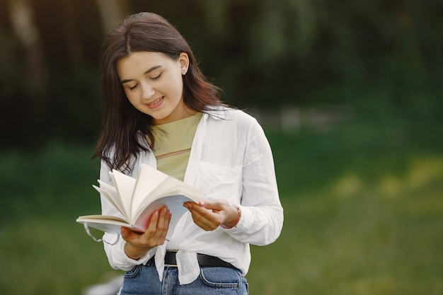 美しい女性の肖像画。女性は本を読んだ。白いシャツを着た女性。