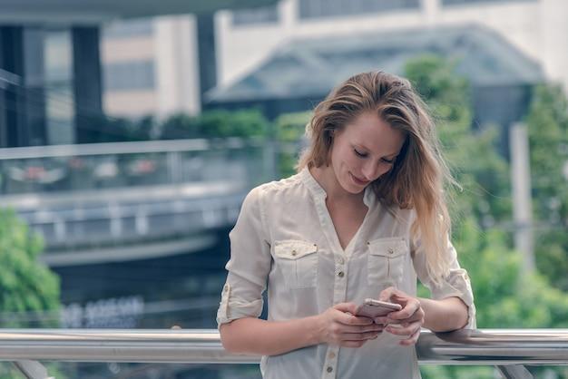 美しい女性の肖像画はスマートフォンを使用しています
