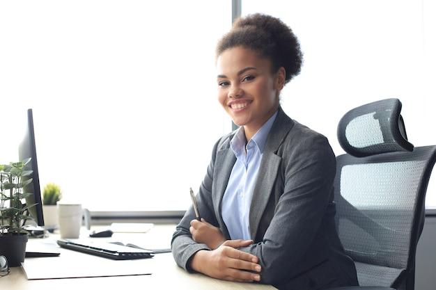 테이블에 앉아 컴퓨터 작업을 하는 아름다운 젊은 아프리카계 미국인 여성의 초상화.