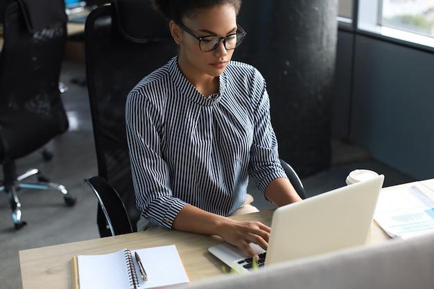 테이블에 앉아 있는 동안 노트북으로 작업하는 아름다운 젊은 아프리카계 미국인 여성의 초상화.