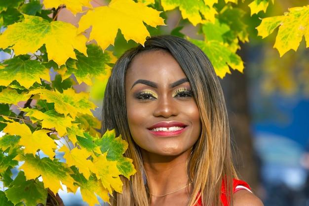 Портрет красивой молодой африканской женщины на осенних листьях