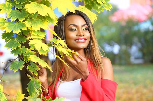 Портрет красивой молодой африканской женщины на поверхности осенних листьев