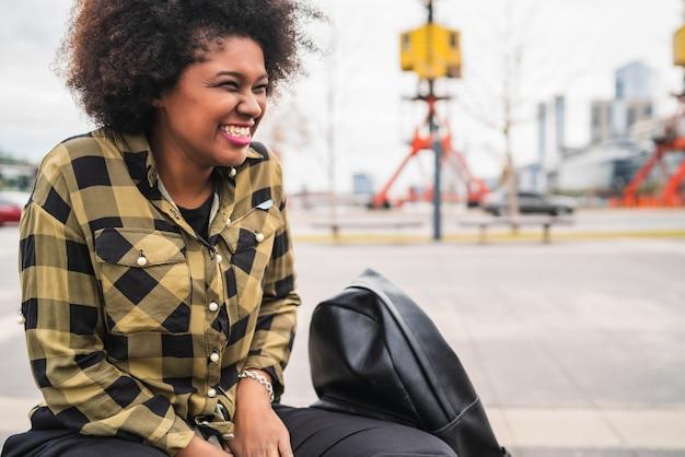 Портрет красивой молодой афро-американской латинской женщины с вьющимися волосами, сидящей на улице на улице.