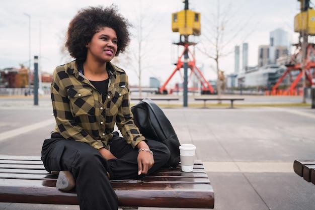 通りの屋外に座っている巻き毛の美しい若いアフロアメリカンラテン女性の肖像画。