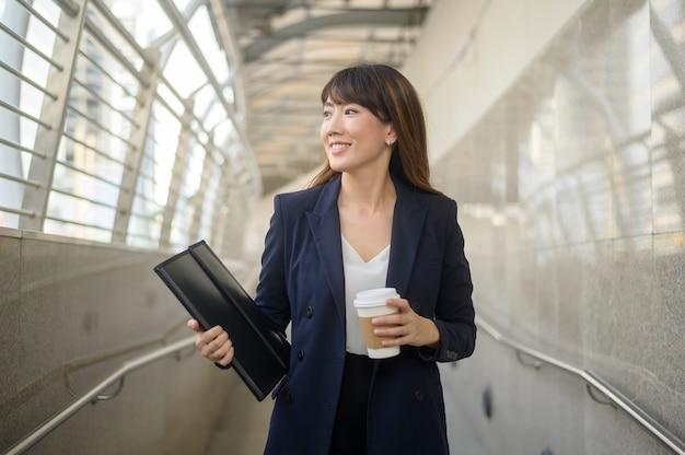 美しい若いアジアのビジネス女性の肖像画は、近代的な都市で働いています