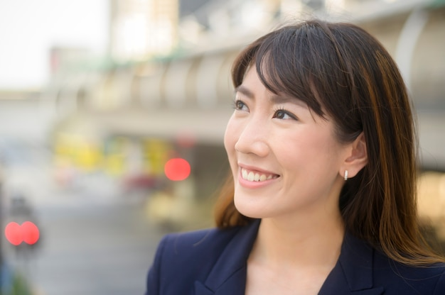 Портрет красивой молодой азиатской бизнес-леди работает в современном городе