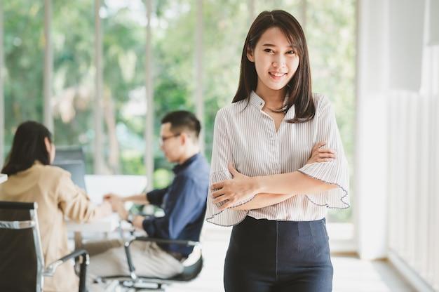 オフィスの会議室でバックグラウンドで同僚と腕を組んで立っている美しい若いアジアの実業家の肖像画