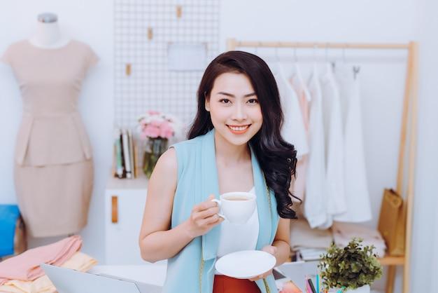 Портрет красивой молодой азиатской модной деловой женщины в своей студии, попивая кофе