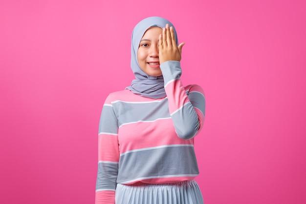 아름 다운 젊은 아시아 여자의 초상화는 분홍색 배경에 손으로 한쪽 눈을 가리고