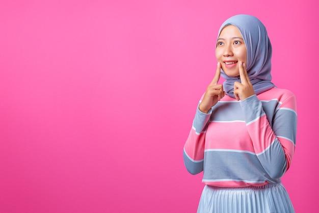 ピンクの背景に陽気で幸せな気持ちの美しい若いアジアの女性の肖像画