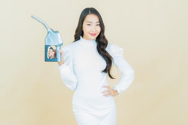 컬러 벽에 아름다운 젊은 아시아 여성 펠 가스 펌프의 초상화