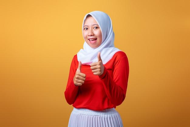黄色の背景に笑顔で親指をあきらめて美しい若いアジアの女性の肖像画