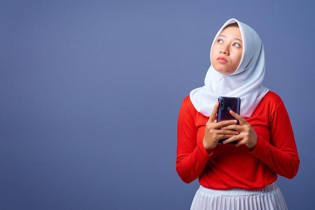 Портрет красивой молодой азиатской женщины, держащей смартфон с выражением мышления и смотрящей вверх