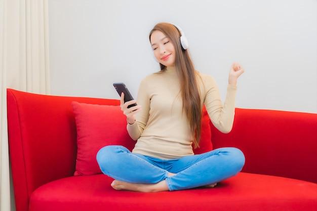 美しい若いアジアの女性の肖像画は、リビングルームのインテリアのソファで音楽を聴きます