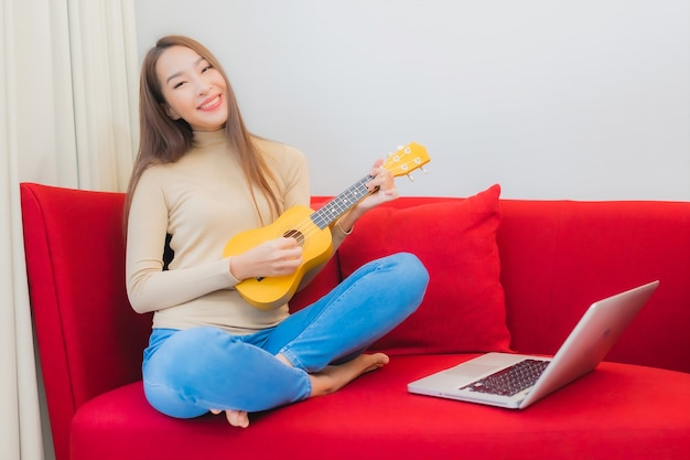 美しい若いアジアの女性の肖像画は、リビングルームのインテリアのソファでウクレレを再生します