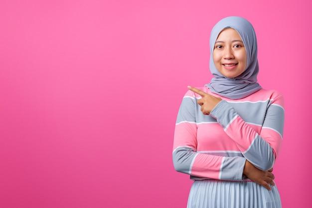 笑顔で空きスペースを指す美しい若いアジアの女性の肖像