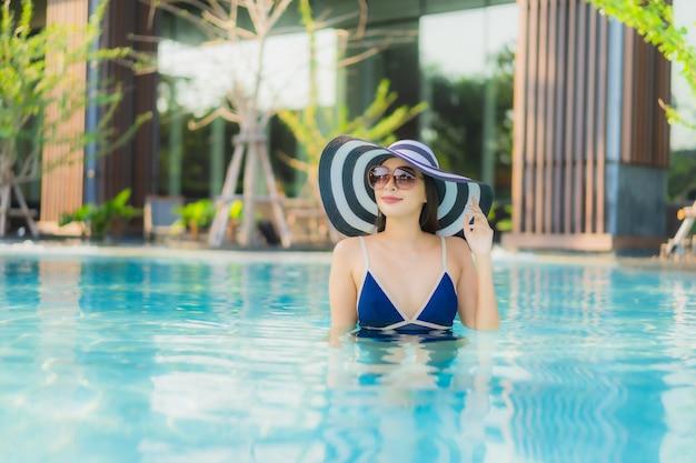 아름 다운 젊은 아시아 여자의 초상화는 호텔 리조트 수영장에서 이완