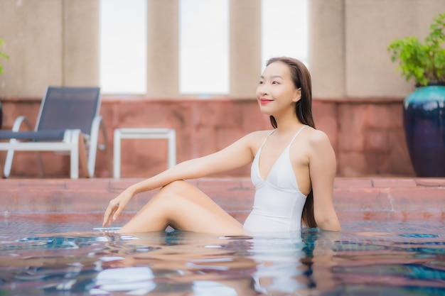 美しい若いアジアの女性の肖像画は、プールでリラックス