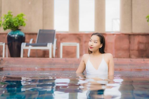 Портрет красивой молодой азиатской женщины расслабляется в бассейне