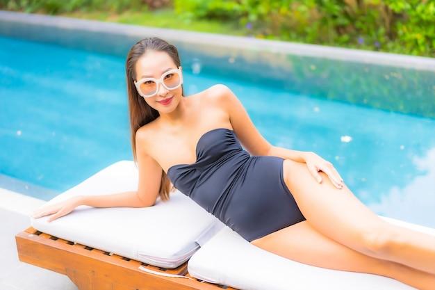 美しい若いアジアの女性の肖像画は、スイミングプールでリラックス