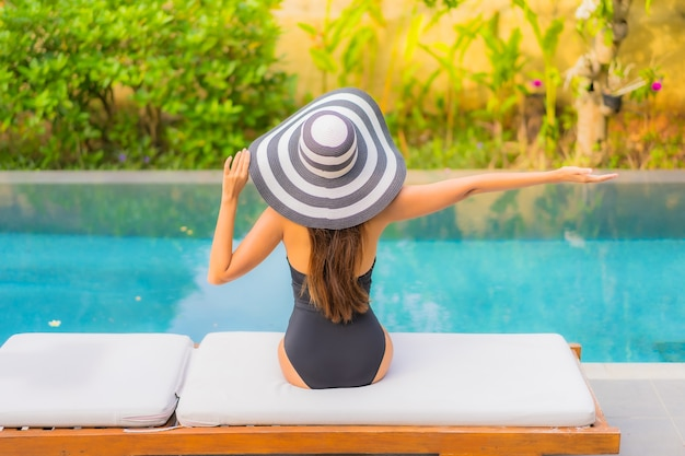 아름 다운 젊은 아시아 여자의 초상화는 수영장에서 이완