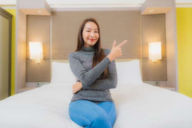 美しい若いアジアの女性の肖像画は、寝室のベッドでリラックス