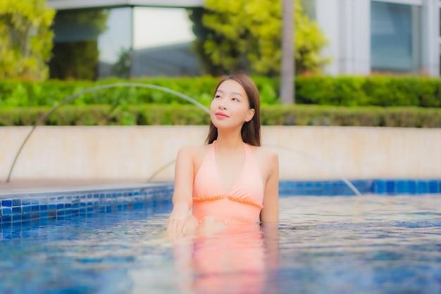 美しい若いアジアの女性の肖像画はホテルリゾートのプールでリラックス