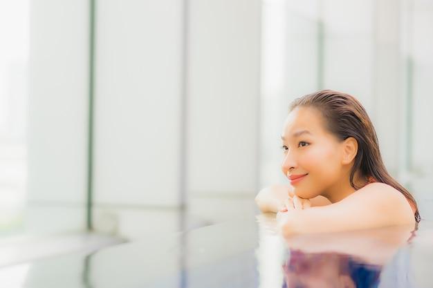 아름 다운 젊은 아시아 여자의 초상화는 호텔 리조트의 수영장에서 이완